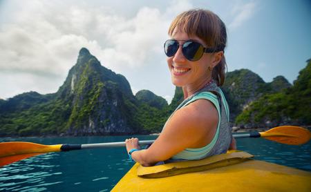 ocean kayak: Se�ora sonriente sentado en el kayak con las monta�as de piedra caliza de la bah�a de Ha Long en Vietnam en el fondo. Foto de archivo