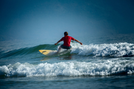 short wave: Surfer riding the wave on the short board at sunny day