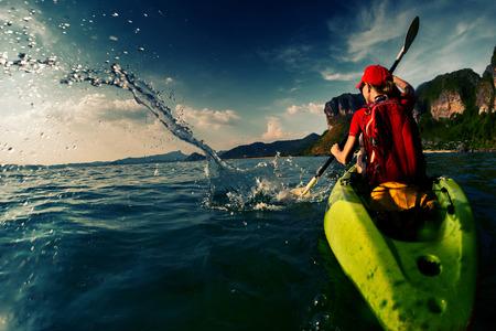 水しぶきをたっぷりと海カヤックを漕ぐハード若い女性