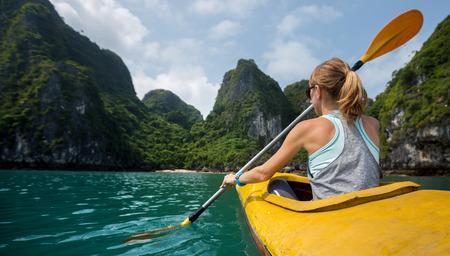 Woman exploring calm tropical bay with limestone mountains by kayak. Ha Long Bay Vietnam Фото со стока