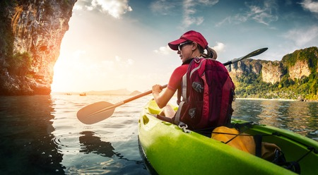 canoeing: Young lady paddling kayak Stock Photo