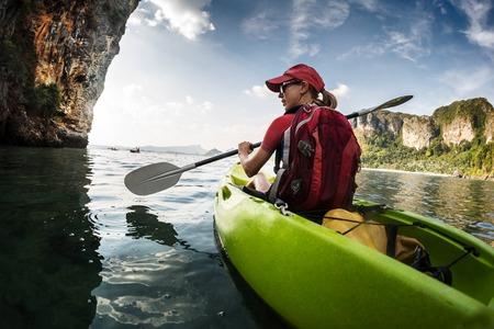 Young lady paddling kayak Standard-Bild