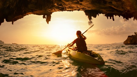 cave: Young lady paddling the kayak Stock Photo