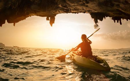 cave exploring: Young lady paddling the kayak Stock Photo