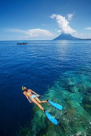 skin diving: Lady snorkeling over reef wall