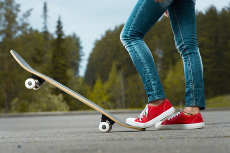 skate board: Lady with red shoes standing on the asphalt road with skate board Stock Photo