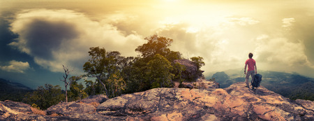 alone person: Panorama of the hiker with backpack standing on the rocky ground of the mountain Stock Photo