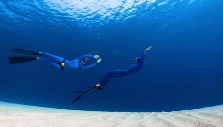 picada: Dos buceadores que se divierten sobre el fondo del mar de arena