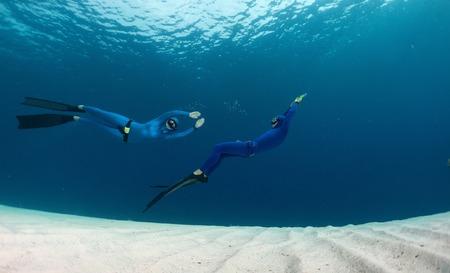 freediving: Two freedivers having fun over the sandy sea bottom