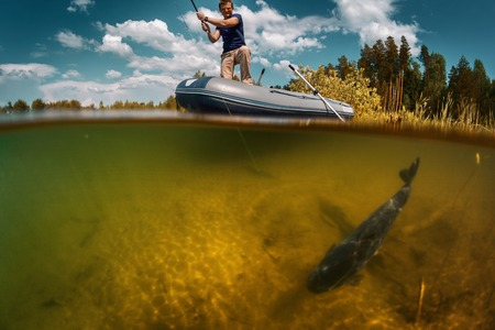 cyprinidae: Split shot of the fisherman with rod in the boat and underwater view of the fish near a bottom Stock Photo