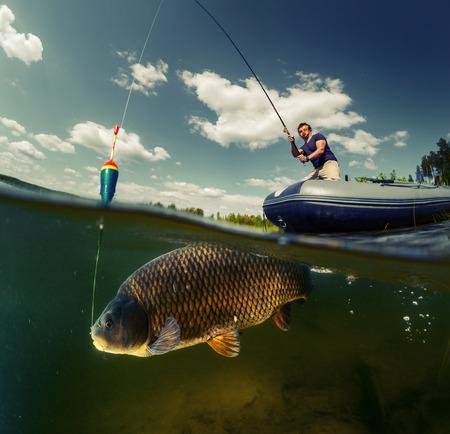 Tiro rachado do pescador com vara no barco e vista subaquática do grande peixe (carpa da família de Cyprinidae)