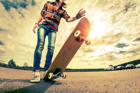 skateboarding tricks: Young lady with skateboard on the road