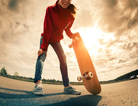 skateboard shoes: Young lady standing with skateboard