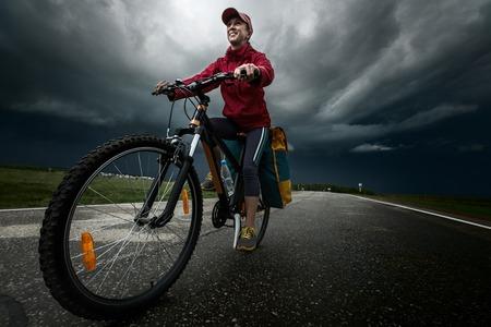 empedrado: Se�ora excursionista que monta la bicicleta cargada en la carretera asfaltada, con nubes de tormenta en el fondo