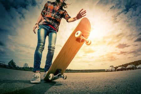 도로에 스케이트 보드와 함께 젊은 아가씨