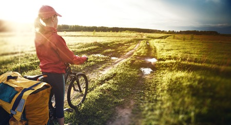 unpaved road: Woman with loaded bicycle on the wet unpaved rural road at sunset