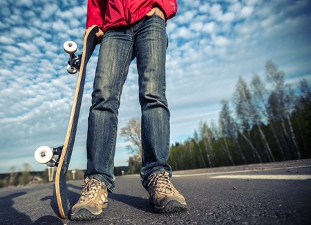 skate board: Rider standing on the asphalt road and holding skate board over the blue sky background