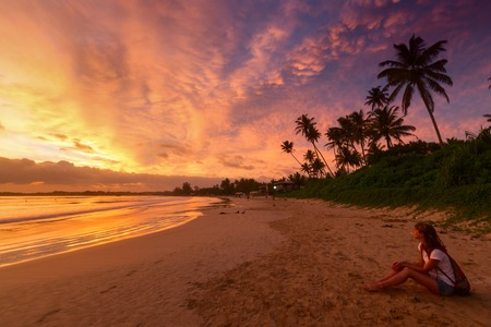girl sit: Young lady relaxing on the tropical beach and enjoying sunset