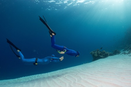 freediving: Two freedivers finning over the sandy sea bottom