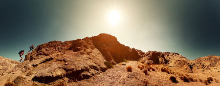 Twee wandelaars beklimmen van de berg in de woestijn