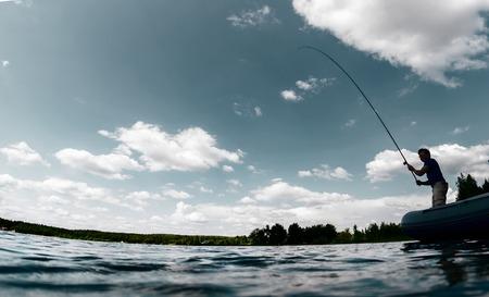 Silhouet van de jonge man vissen op het frisse water vijver Stockfoto