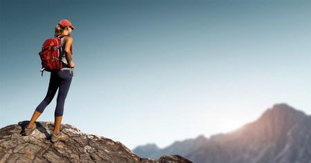 rural: Lady hiker standing on top of the hill with clear sky and mountains on the background Stock Photo