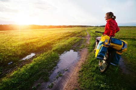 carrying the cross: Lady hiker standing on the wet road with loaded bicycle Stock Photo