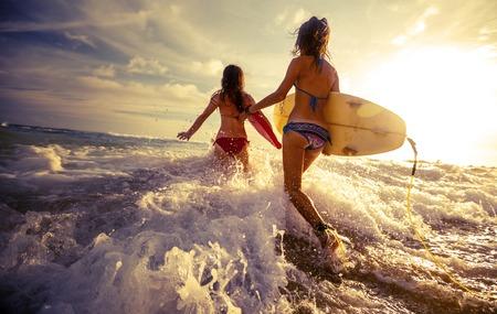 jeune fille: Deux dames de course dans la mer avec des planches de surf