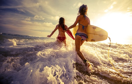 two: Two ladies running into the sea with surf boards