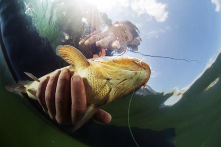 魚を手にする漁師の水中撮影