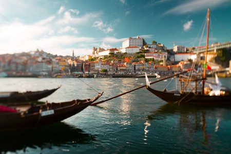 roof light: Traditional portuguese boats on the river of Douro with the city of Porto on the background. Tilt shift lens used with focus on the middle of shot