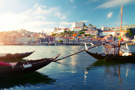 tilt and shift: Traditional portuguese boats on the river of Douro with the city of Porto on the background. Tilt shift lens used with focus on the middle of shot