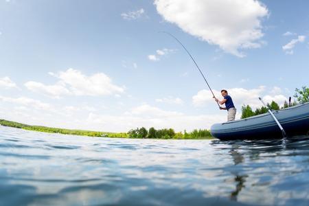 dia soleado: Pesca del hombre joven en el estanque de agua fresca en el día asoleado