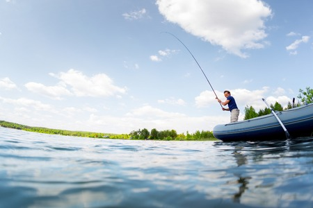 fishing: Young man fishing on the fresh water pond at sunny day