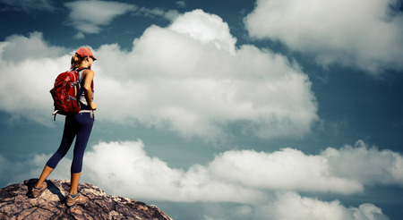 top mountain: Lady hiker standing on top of the mountain over the cloudy sky background Stock Photo