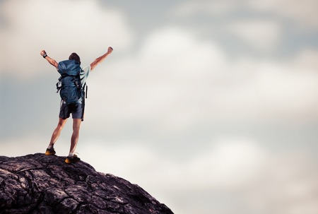 rock climbing man: Hiker with backpack standing on top of the mountain with raised hands Stock Photo