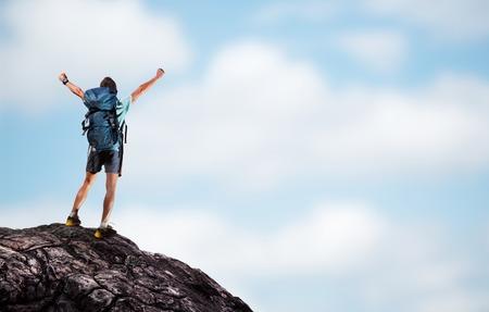 escalada: Caminante con mochila de pie en la cima de la monta�a con las manos levantadas