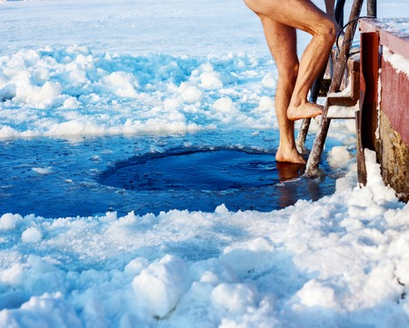 ice cold: Man is going to swim in the ice hole at sunny day Stock Photo