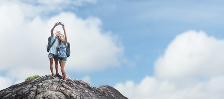 rock climbing: Couple of hikers with backpacks taking selfie on top of the mountain