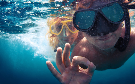 a ok: Young couple having fun underwater and showing ok sign