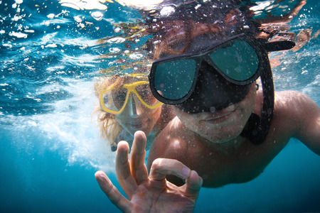 water bubbles: Young couple having fun underwater and showing ok sign