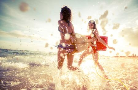 Twee dames lopen in de zee met surfplanken