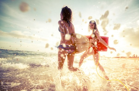 friend: Two ladies running into the sea with surf boards