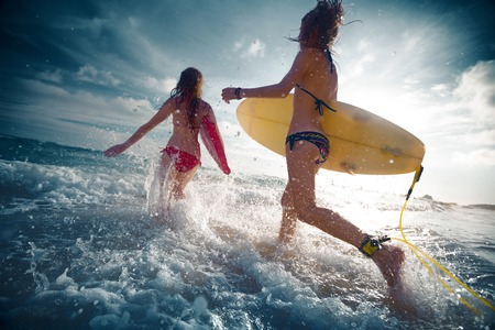 surf board: Two ladies running into the sea with surf boards