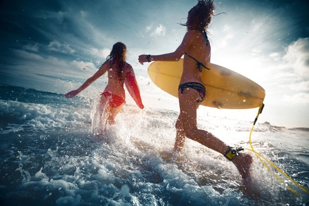 surfing: Two ladies running into the sea with surf boards