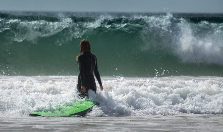 surf board: Lady surfer walking with surf board towards the ocean Stock Photo