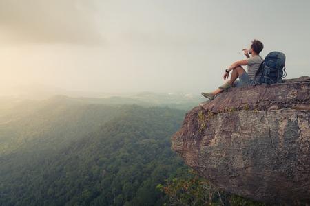 Wandelaar ontspannen op de top van de berg en het drinken van gebotteld water