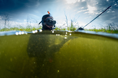 spearfishing: Man with spear gun preparing on the surface before spearfishing in the fresh water pond with poor visibility Stock Photo