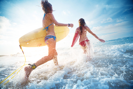 Duas senhoras correndo para o mar com pranchas de surf