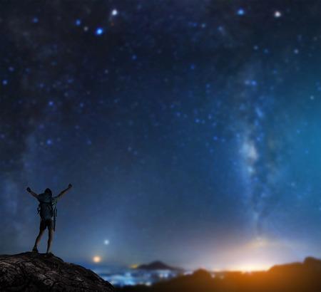 ハイカー バックパック背景に星空の上げられた手の山の頂上に立って、